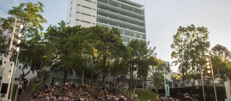 foto do campus da pucrs, prédio com escadaria e jovens sentados
