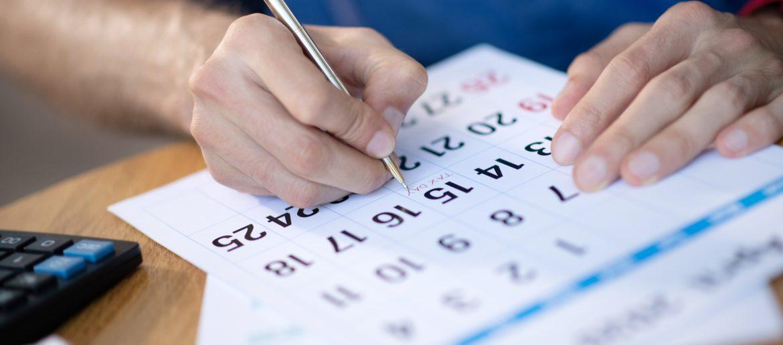 imagen de manos escribiendo en las fechas de una agenda